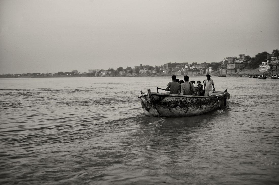 Pequeno barco com indianos a navegar nas águas do rio Ganges em Varanasi.
