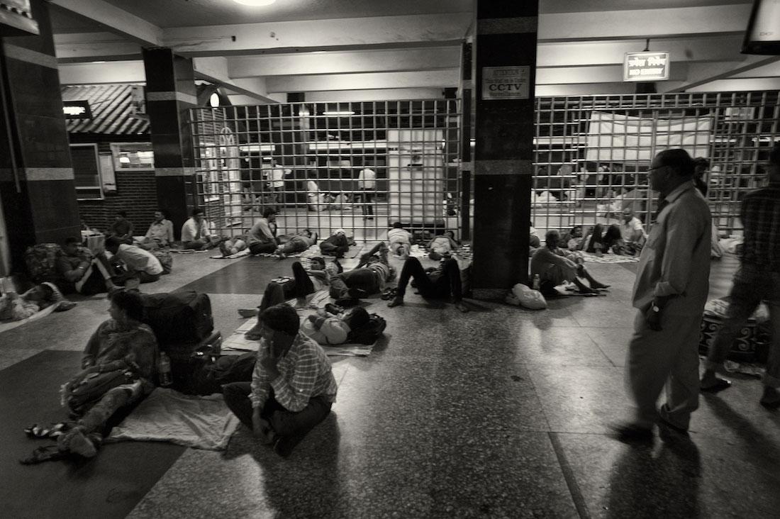 Várias pessoas sentadas ou deitas numa sala de espera na estação de comboios de Delhi.
