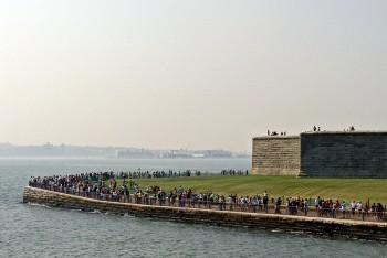 Muitas pessoas na extremidade da Liberty Island junto à base da estátua da liberdade.