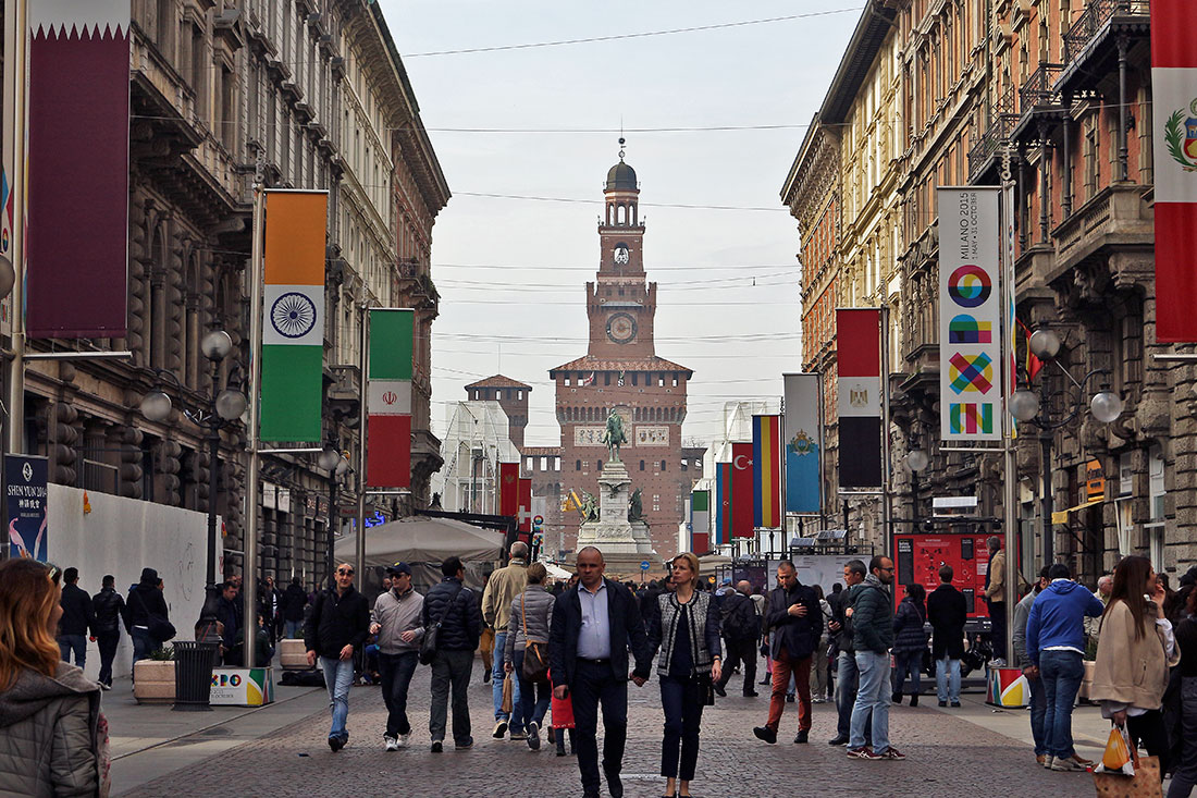 Rua Dante, cheia de pessoas a passear, com castelo Cairoli ao fundo