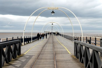 Pessoas a caminhar no pier da praia de southport, perto de Liverpool.
