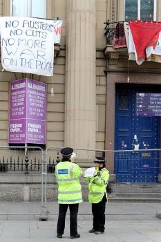 Policias junto a prédios com faixas de protesto no centro de Liverpool.