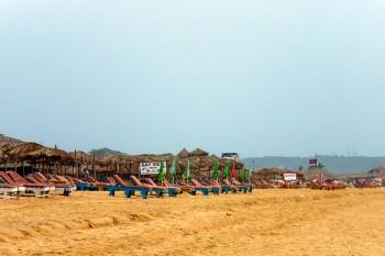 Areal e cabanas de palha na praia em Candolim, norte de Goa, Índia