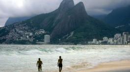 Dois rapazes a sair do mar na praia de Ipanema debaixo de um dia muito nublado.