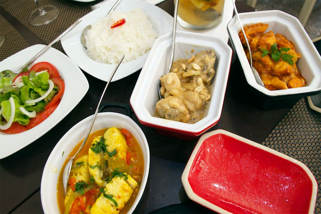 Pratos de frango de amendoim, abacate com atum e moqueca de peixe, acompanhados por arroz, no restaurante língua