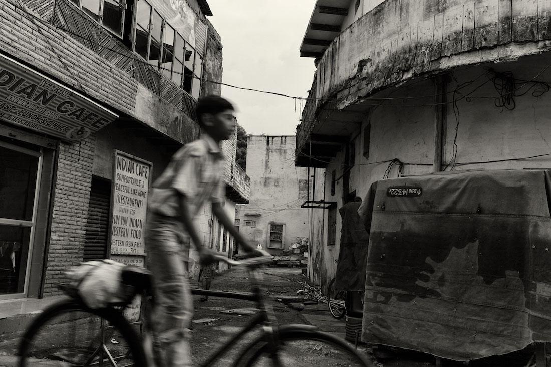 Rapaz a conduzir uma bicicleta numa rua de Agra.