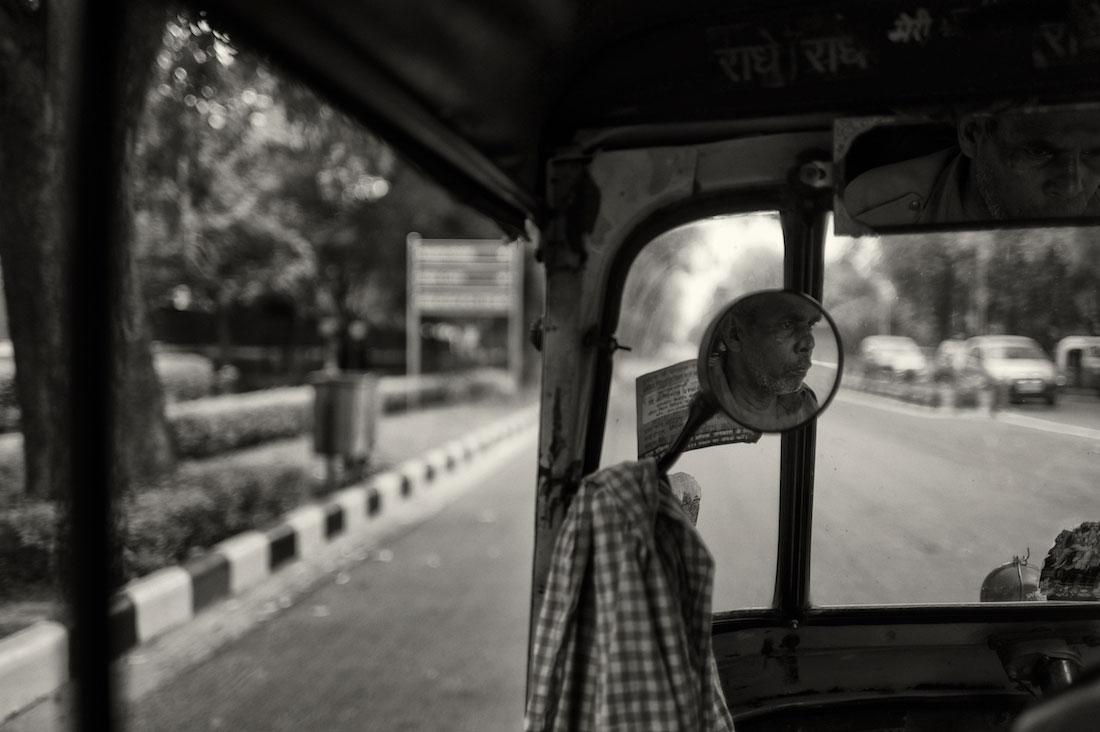Reflexo de um condutor de rickshaw num espelho retrovisor.