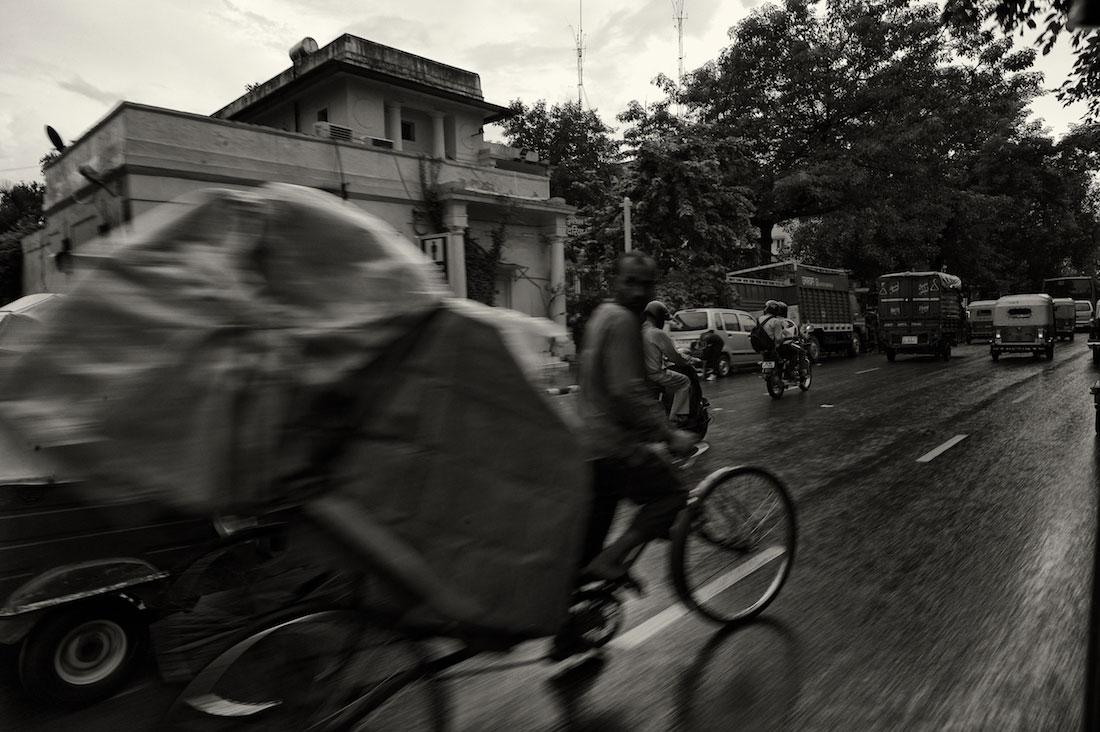 Rickshaw a transportar grande volume de carga numa rua de Nova Delhi.