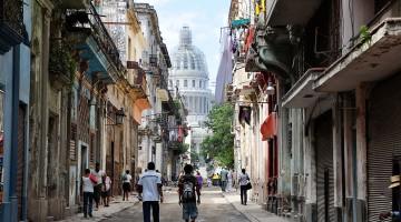 Pessoas numa rua de Havana Vieja com capitólio ao fundo.