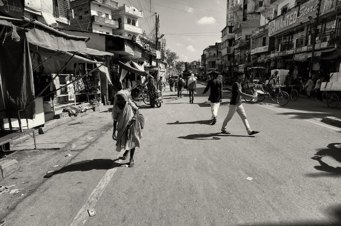 Rua de Varanasi com transeuntes e senhora idosa, envolvida em vários panos, a caminhar.