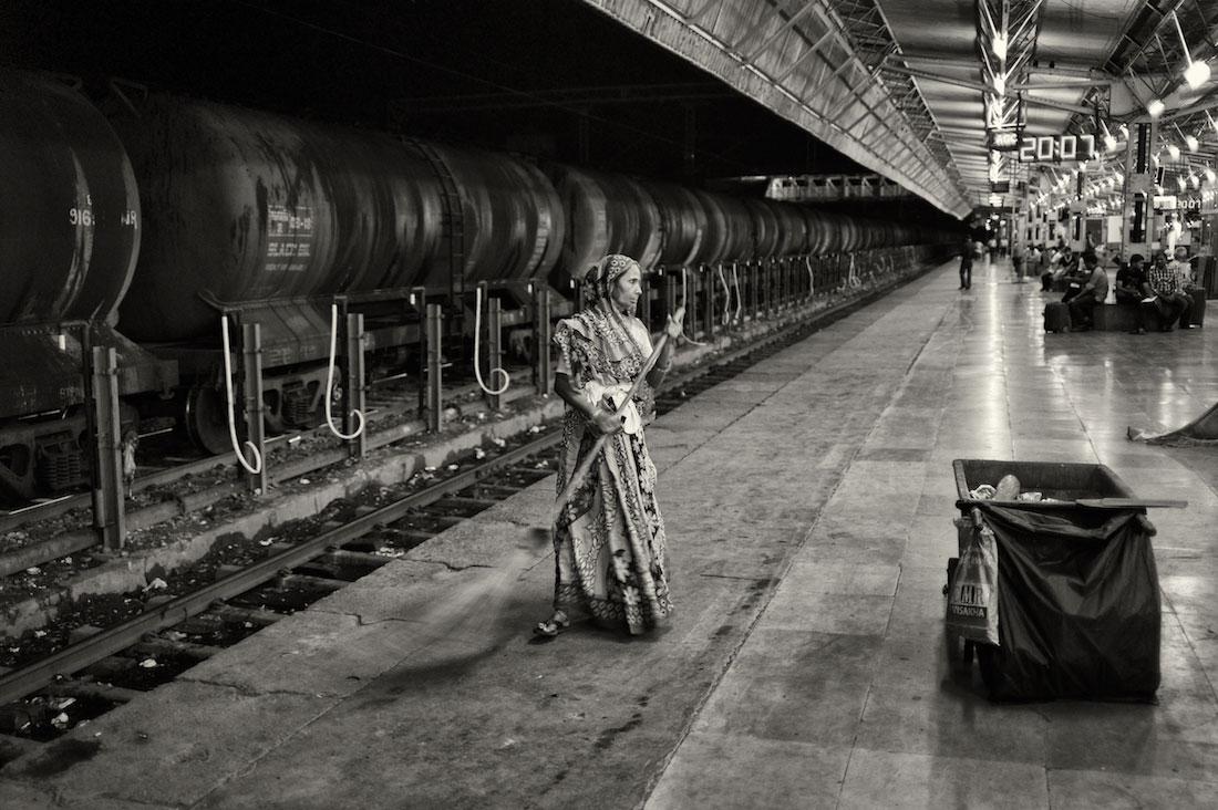 Senhora a varrer o chão do cais na estação de comboios de Agra na Índia.
