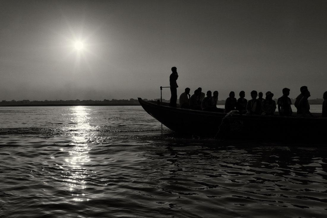 Silhueta de um barco cheio de turistas indianos, no rio Ganges, ao nascer do Sol.