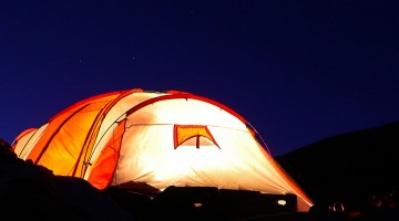 Interior de tenda iluminado durante a noite.