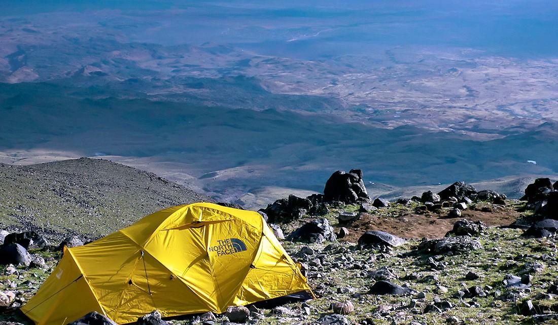 Tenda amarela da North Face instalada numa encosta do monte Ararat com vista para o vale.