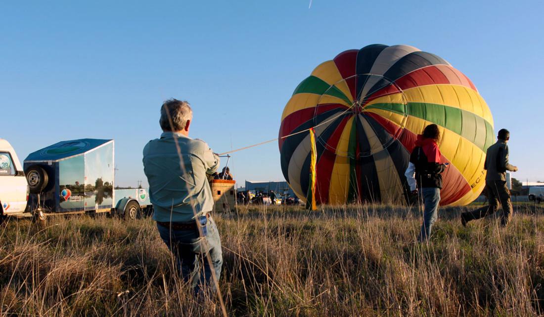 Balonista puxa grande balão colorido enquanto este se enche de ar quente.