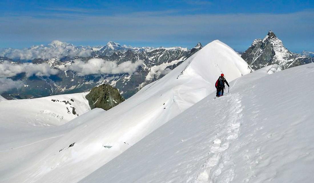 Alpinista isolado a caminhar sobre o tapete de neve existente na aresta do Breithorn