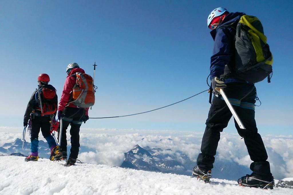 Grupo de alpinistas equipados com crampons e presos por cortas a caminha sobre a neve do Breithorn