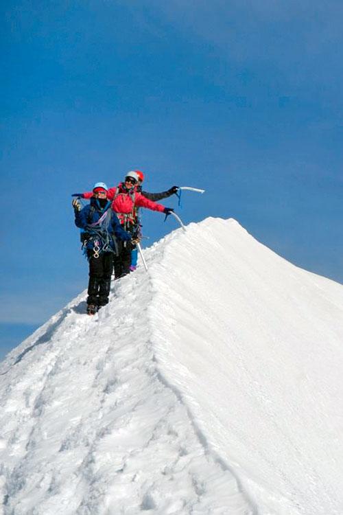 Alpinistas pousam para a fotografia no topo do Breithorn coberto de neve.
