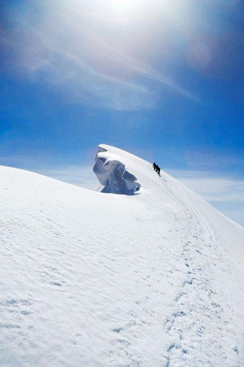 Alpinistas a subida uma cornija coberta de neve na aresta do Breithorn