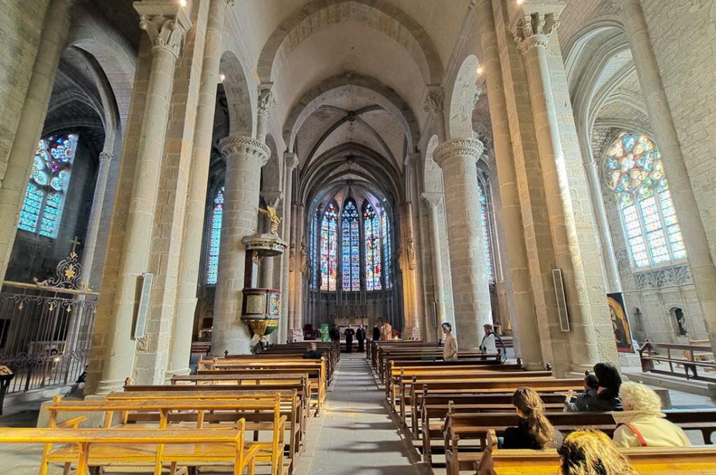 Pessoas sentadas na nave central da basílica de Saint-Nazaire e Saint-Celse em Carcassonne.