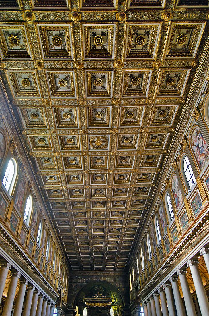 Nave central da basílica de Santa Maria Maior, ladeada de colunas e um rico tecto dourado, em Roma.