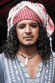 Beduíno de cabelo comprido com lenço vermelho na cabeça e olhos pintados.