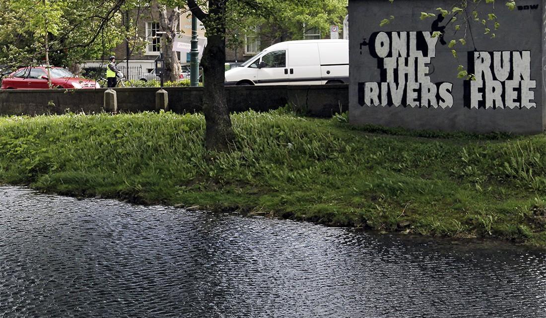 Carros e ciclista junto a parte de um braço de rio no centro de Dublin.