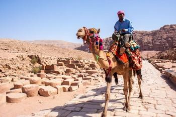 Homem e camelo sobre a via colunata em Petra.
