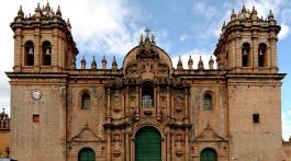 Catedral em pedra alaranjada com duas torres sineiras em Cuzco