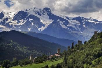 Chaminés de aldeia em Mestia, na Geórgia, com montanhas do Cáucaso ao fundo e envolvente com vegetação muito verde.
