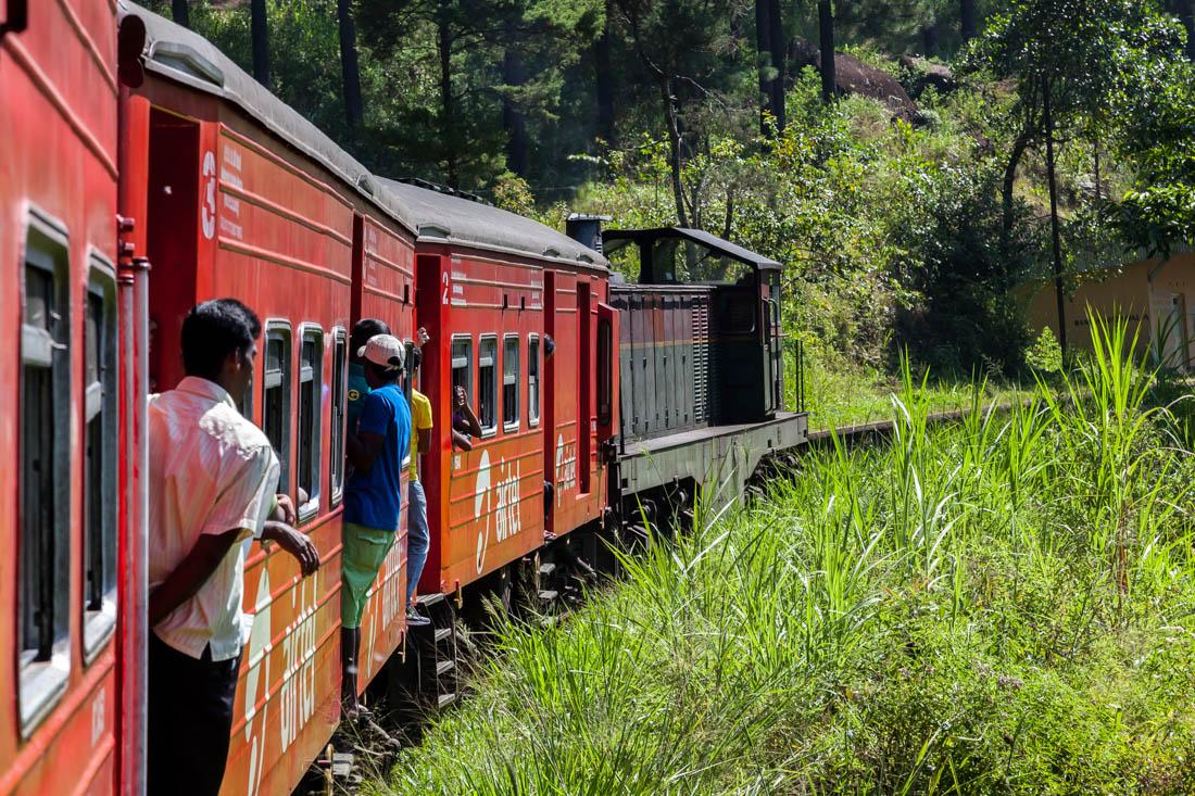 Comboio vermelho com pessoas penduradas a atravessar a montanha no centro do Sri Lanka até a cidade de Ella.