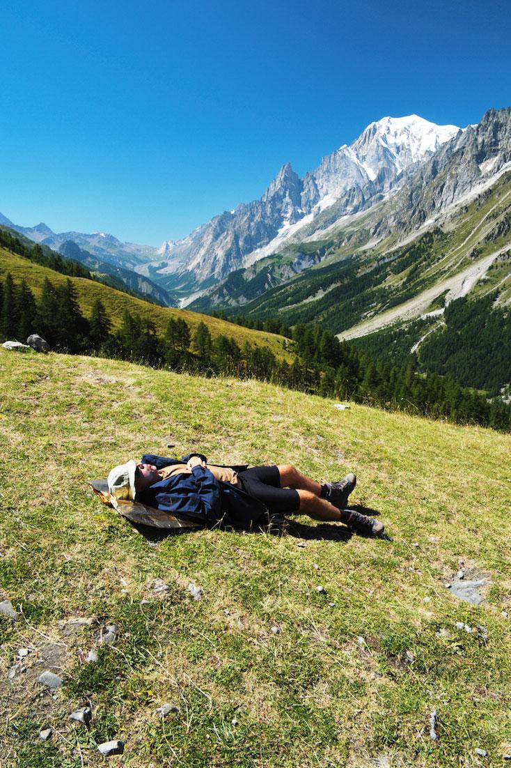 Envolvente do Monte Branco com montanhista a descansar sobre a relva de uma colina.