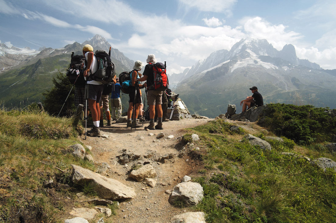 Grupo de montanhistas observa o Maciço do Monte Branco junto a um vale.