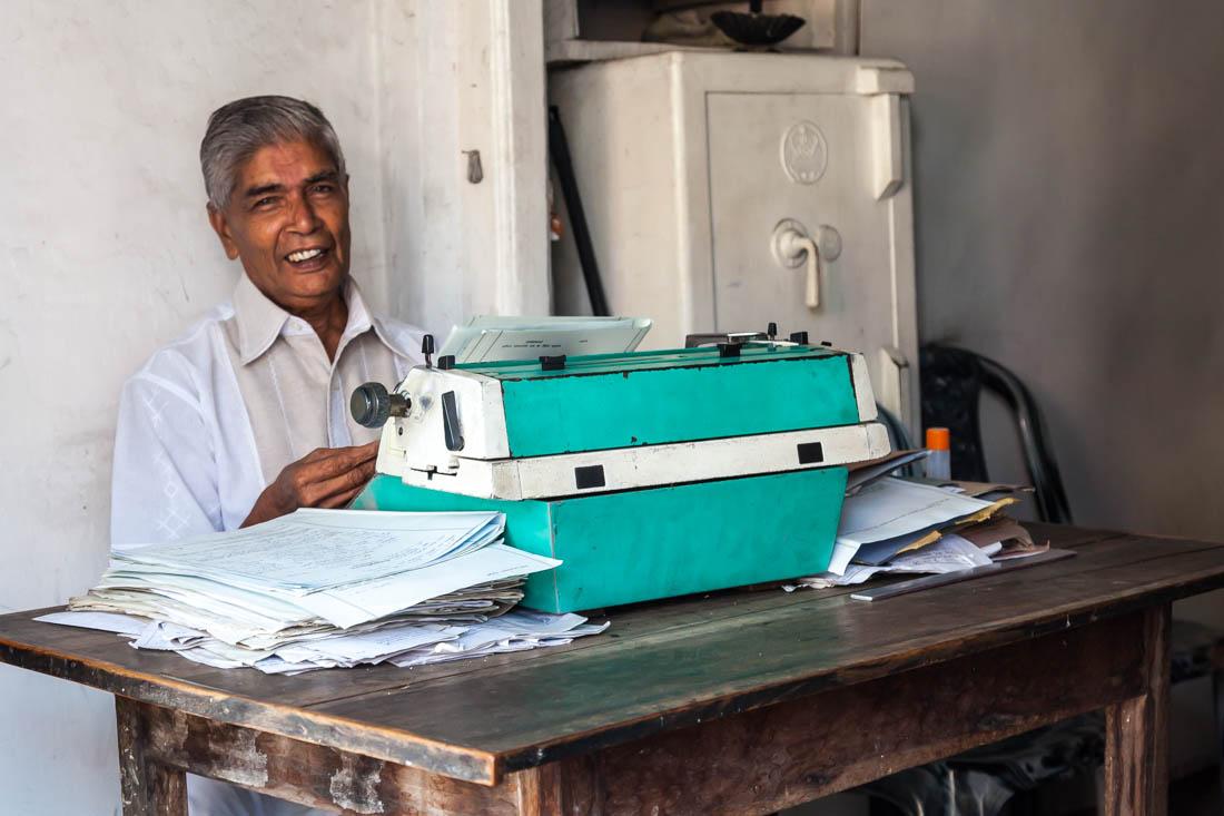 Homem frente a uma máquina de escrever muito antiga num escritório de Tangalle no Sri Lanka.