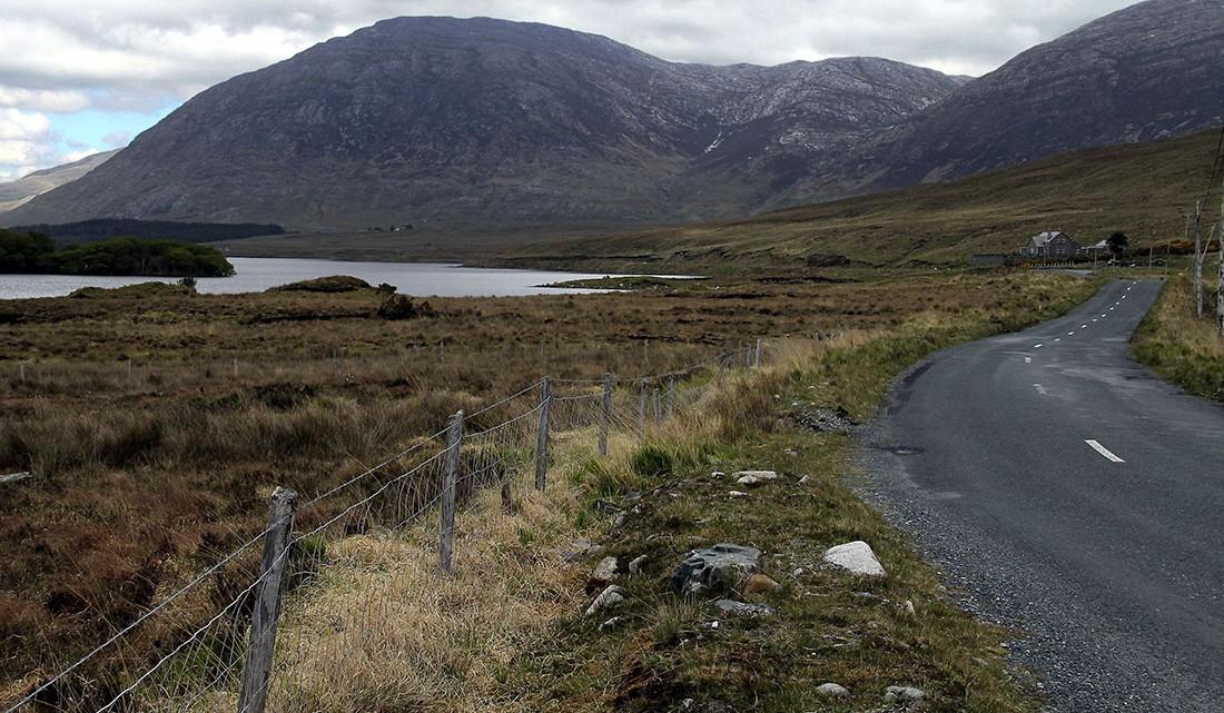 Estrada sinuosa junto a um lago e montanhas no parque nacional de conemara na Irlanda.