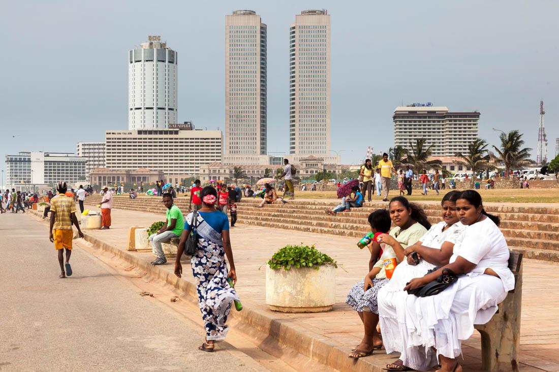 Pessoas sentadas na principal avenida junto ao mar em Colombo, a Galle Face.