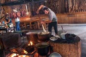 Homem a preparar comina num restaurante Abecázio.