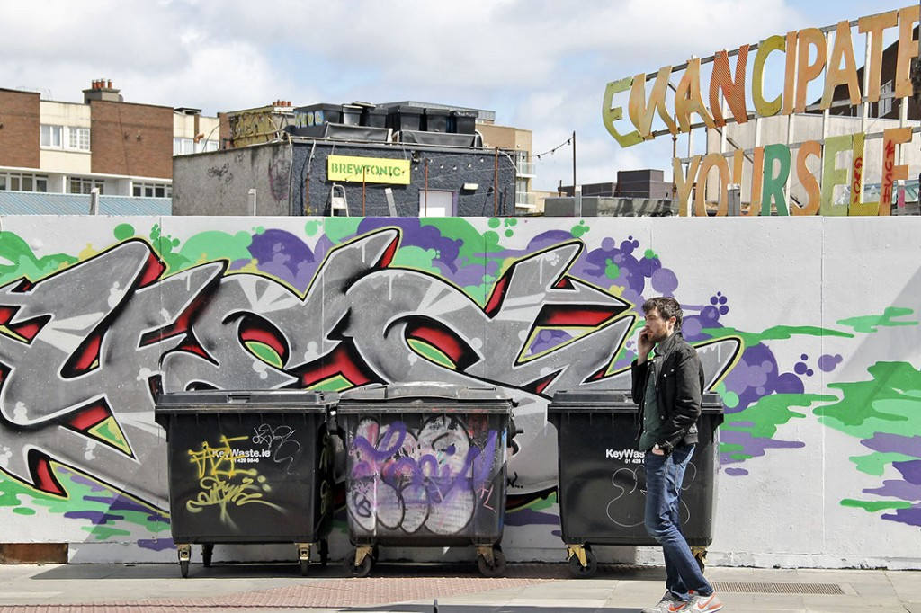 Homem ao telemóvel frente a caixotes do lixo e um mural em Dublin.
