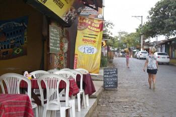 Transeuntes numa estrada da cidade de Itacaré junto a um restaurante.