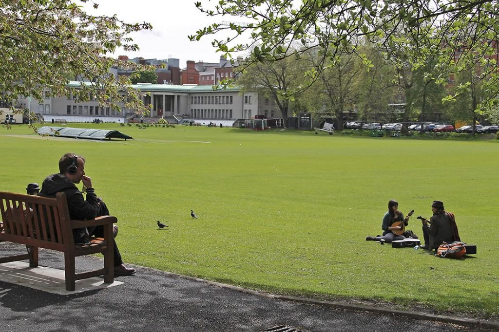 Homem sentado e dois músicos no relva verde dos jardins do Trinity College em Dublin.