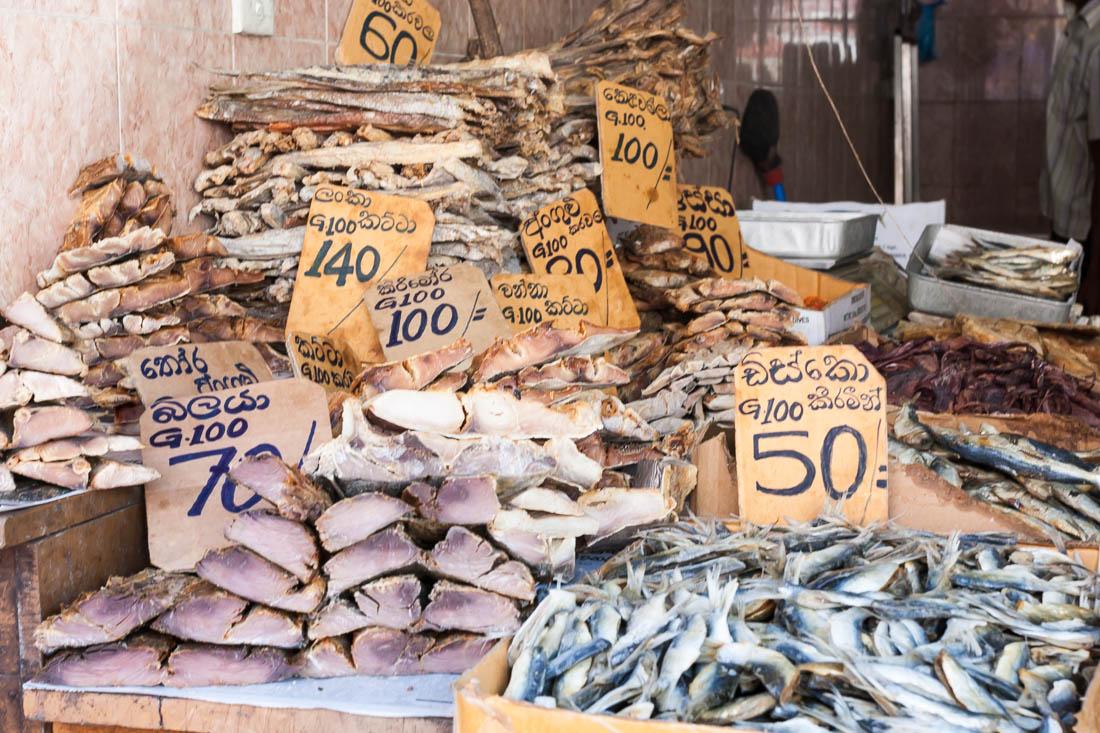 Caixas com peixe seco e placas de cartão com preços numa loja do centro da cidade de Kandy, Sri Lanka.