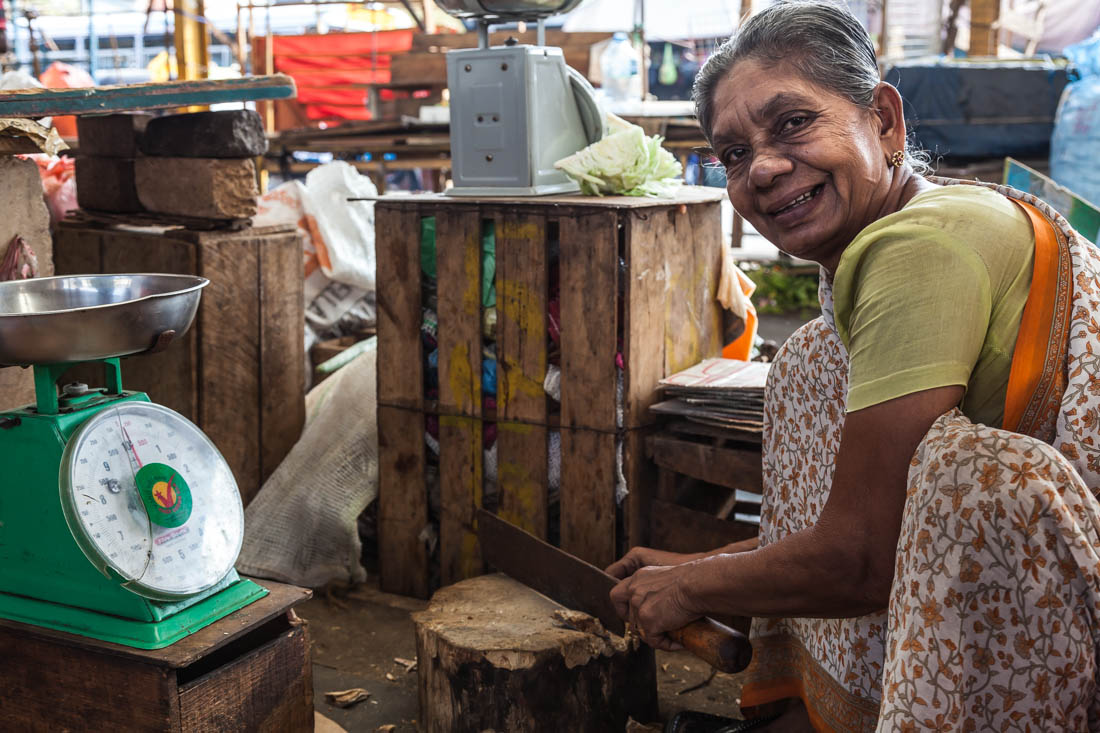 """Vendedora a cortar peixe seco no mercado junto ao """"Old City Hal"""" em Colombo."""