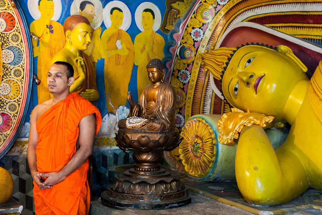 Monge junto a vários budas no Brazen Ppalace em Anaradhpura, Sri Lanka.
