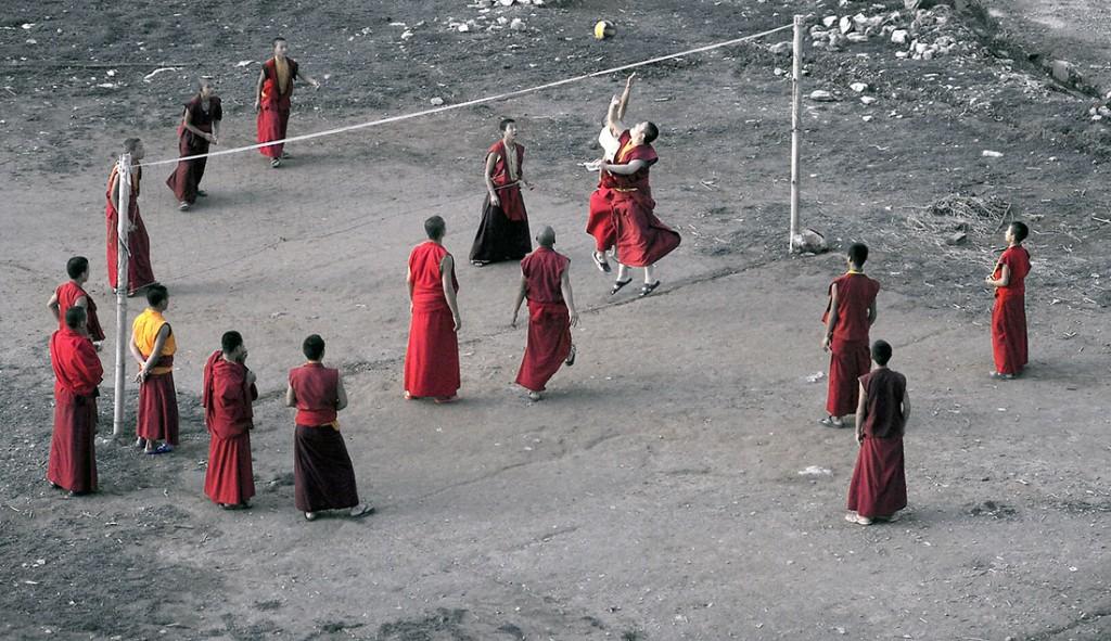 Monges budistas a jogar voleibol num terreiro com barreira feita de dois paus e uma corda.