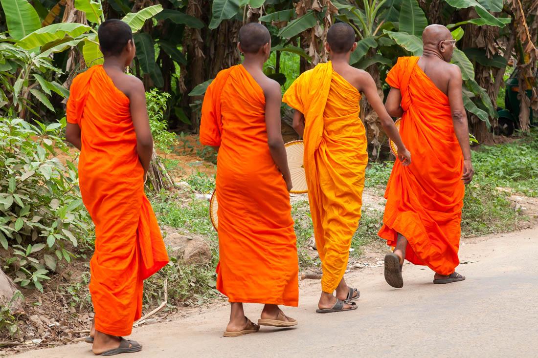 Monges budistas a caminhar numa estada de Unawatuna.