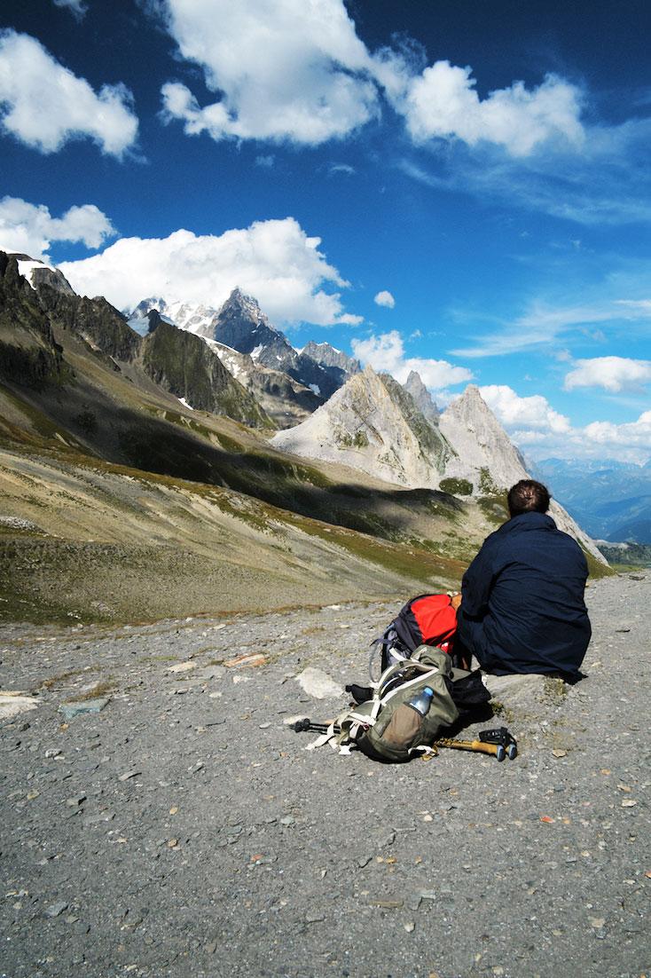 Montanhista sentado num col aprecia a paisagem na região do Monte Branco.