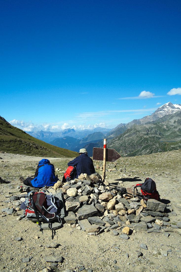 Montanhista sentado numa mariola junto a placa identificadores observa a paisagem natural do Monte Branco.