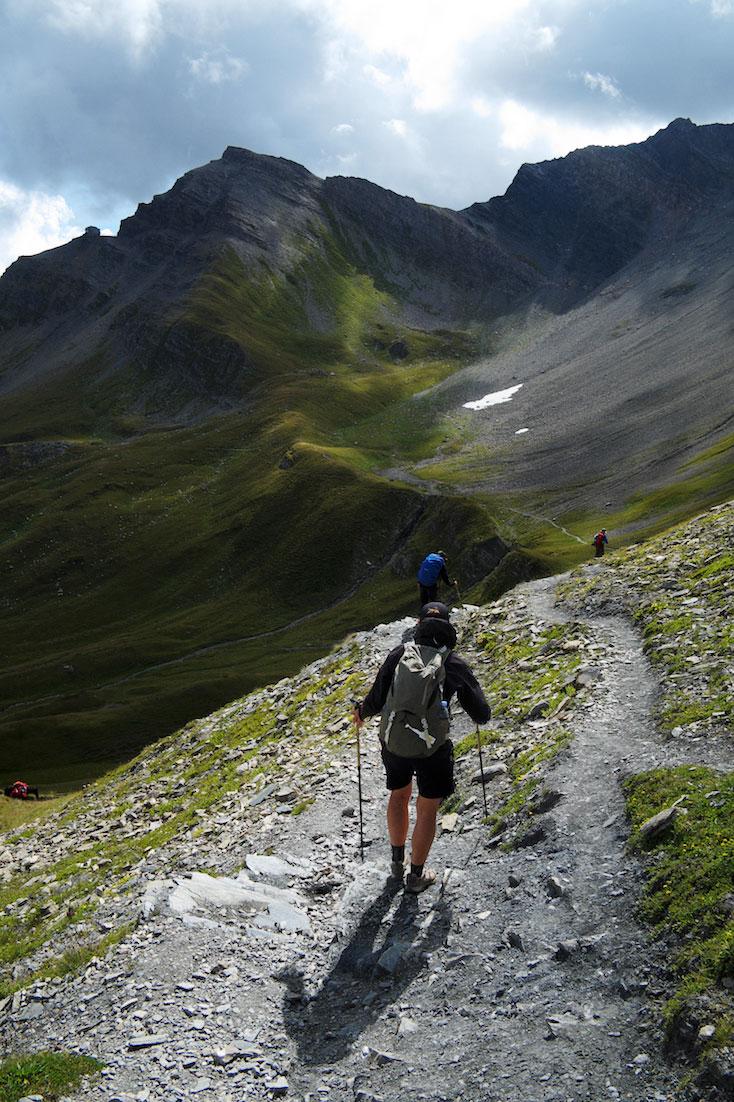 Vários montanhistas descem trilho numa colina acentuada no maciço do monte branco.
