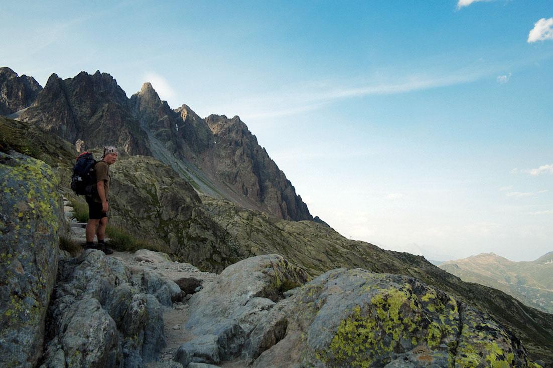 Montanhista parado nos picos do trilho das aiguilles rouges.