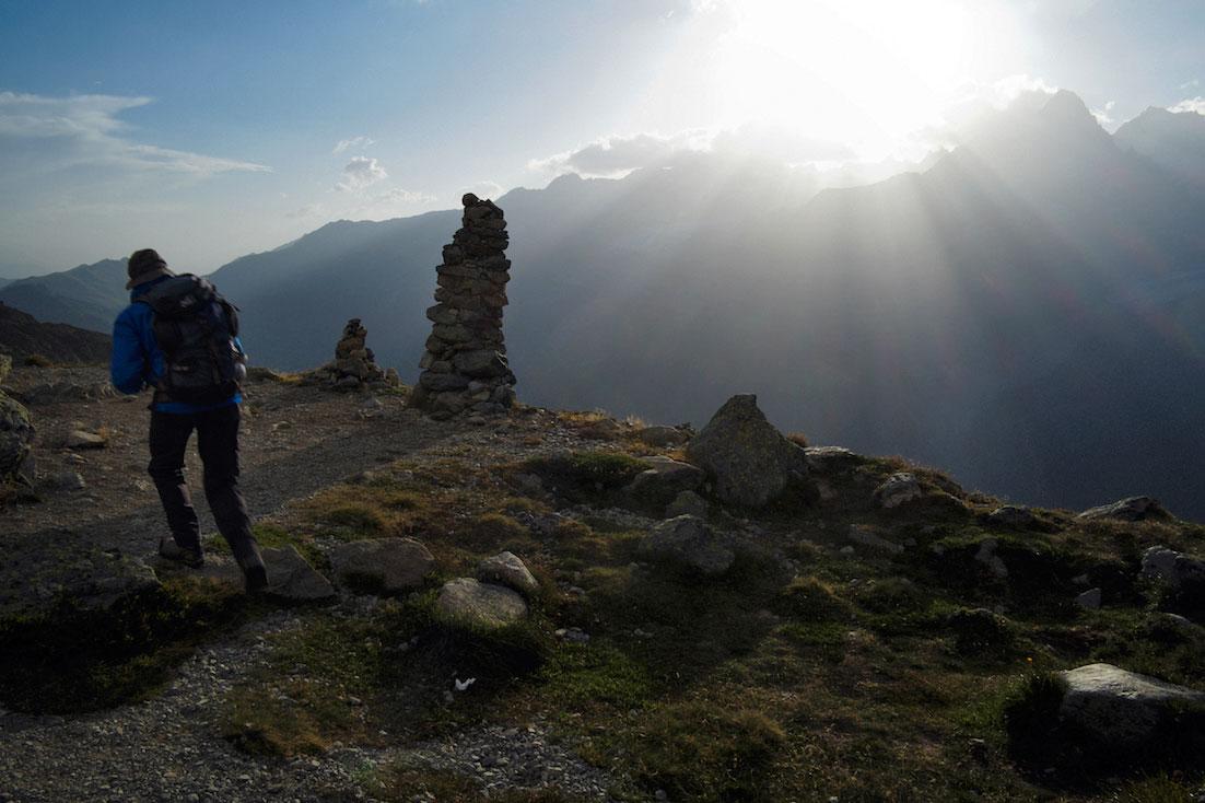 Montanhista e mariolas colocadas junto a um desfiladeiro durante o nascer do sol no maciço do monte branco.